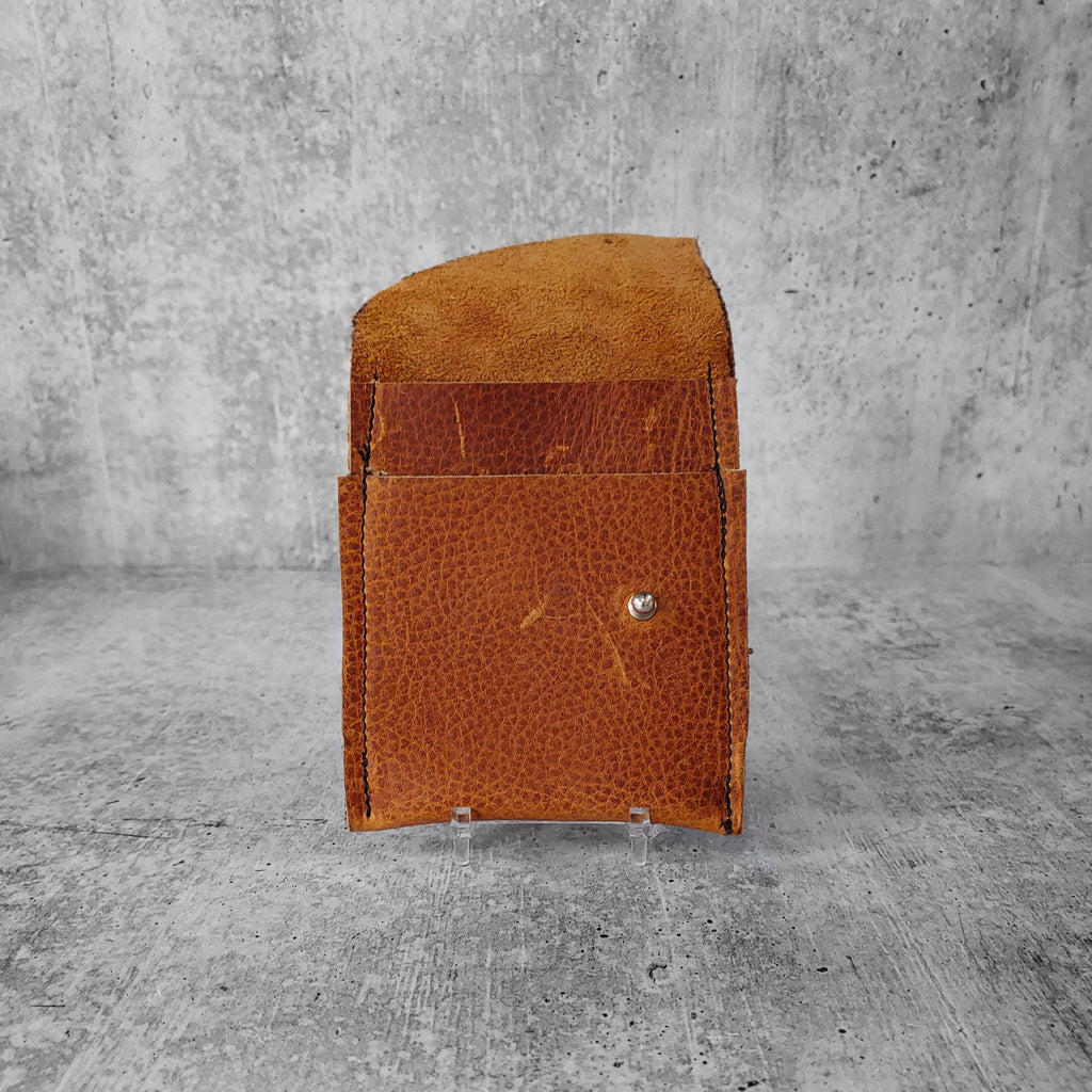 "Open front facing view of ""leather wallet midi right"" in pecan brown against a concrete background. Inside pockets visible."