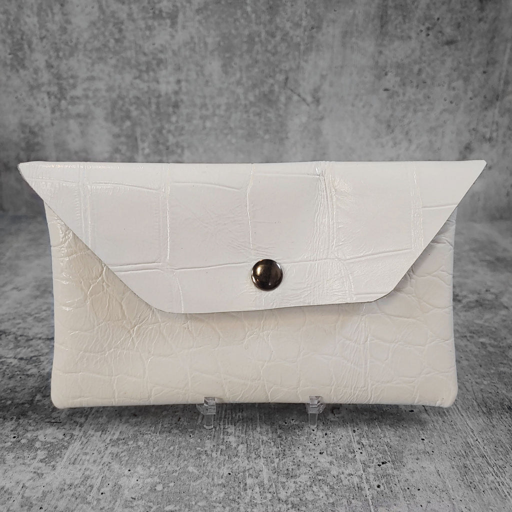 "Front facing view of ""leather wallet trapezoid"" in white against a concrete background."