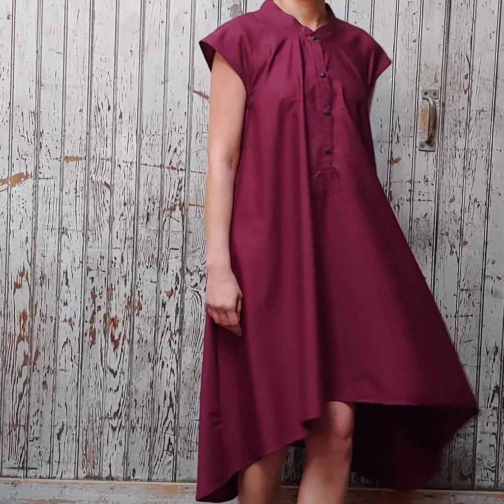 Model wearing McCULLOUGH button down Rambla swing dress in merlot poplin cotton at Harkensback. Features nehru collar.