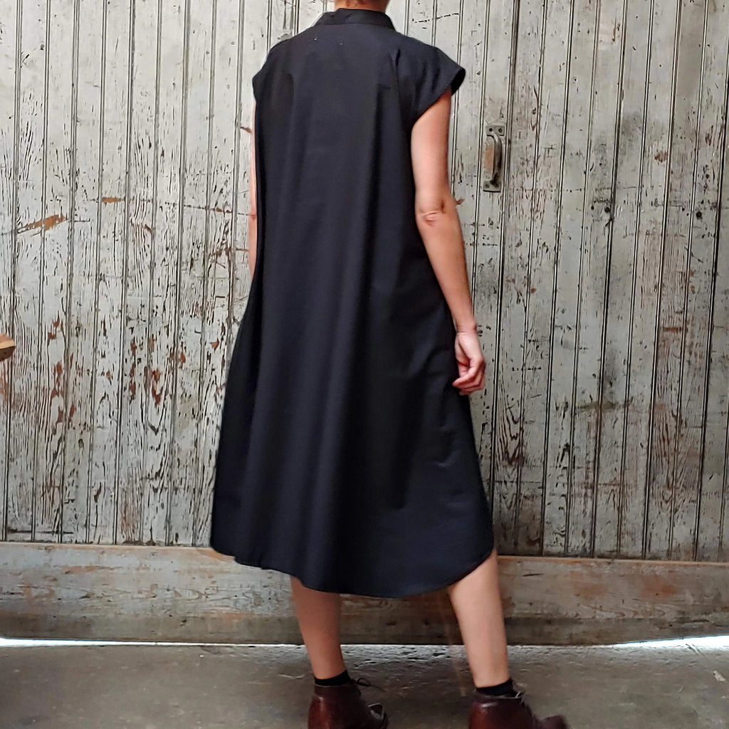 Back view of model wearing McCULLOUGH button down Rambla swing dress in black poplin cotton at Harkensback.