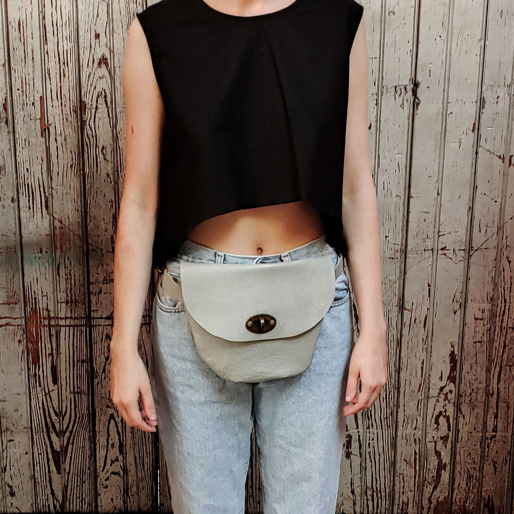 "Front facing view of model wearing ""medium pebbled hip bag"" in urban grey against a wood paneled background."
