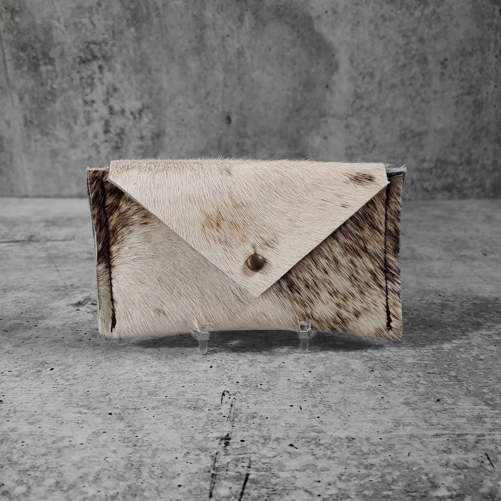 "Front facing view of ""raw hide card holder"" in natural against a concrete background."
