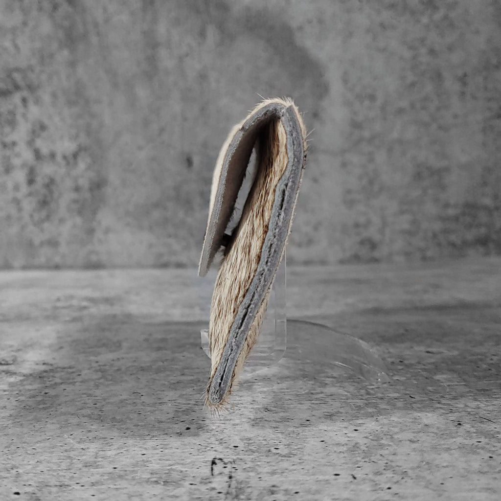 "Side view of ""raw hide card holder"" in natural against a concrete background."