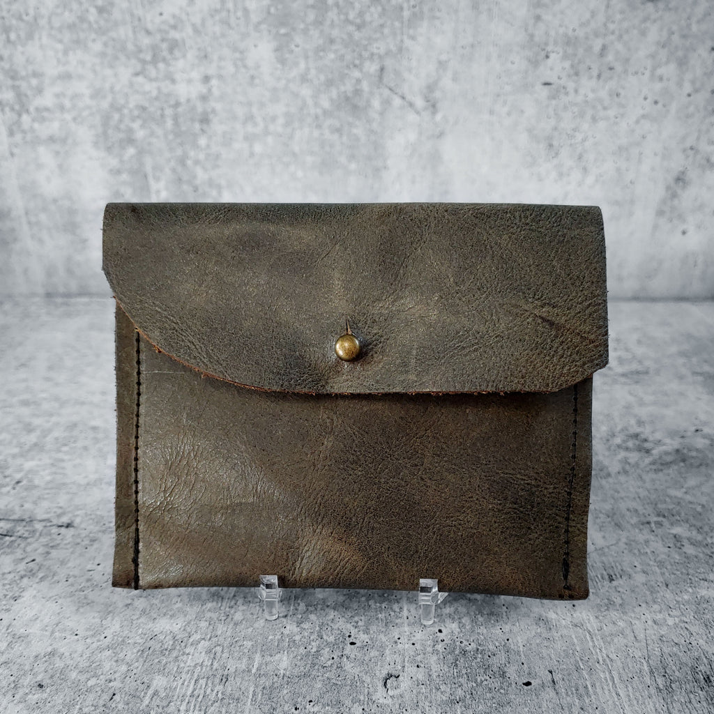 "Front facing view of ""raw leather wallet"" in dark olive against a concrete background."