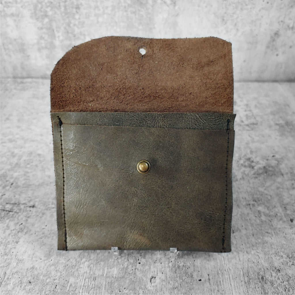 "Open view of ""raw leather wallet"" in dark olive against a concrete background. Inside pockets visible."