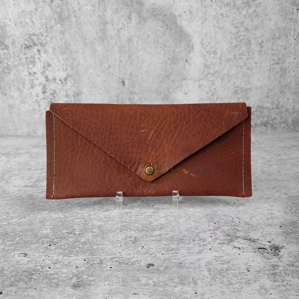 "Front facing view of ""slim leather wallet"" in kodiak brown against a concrete background."