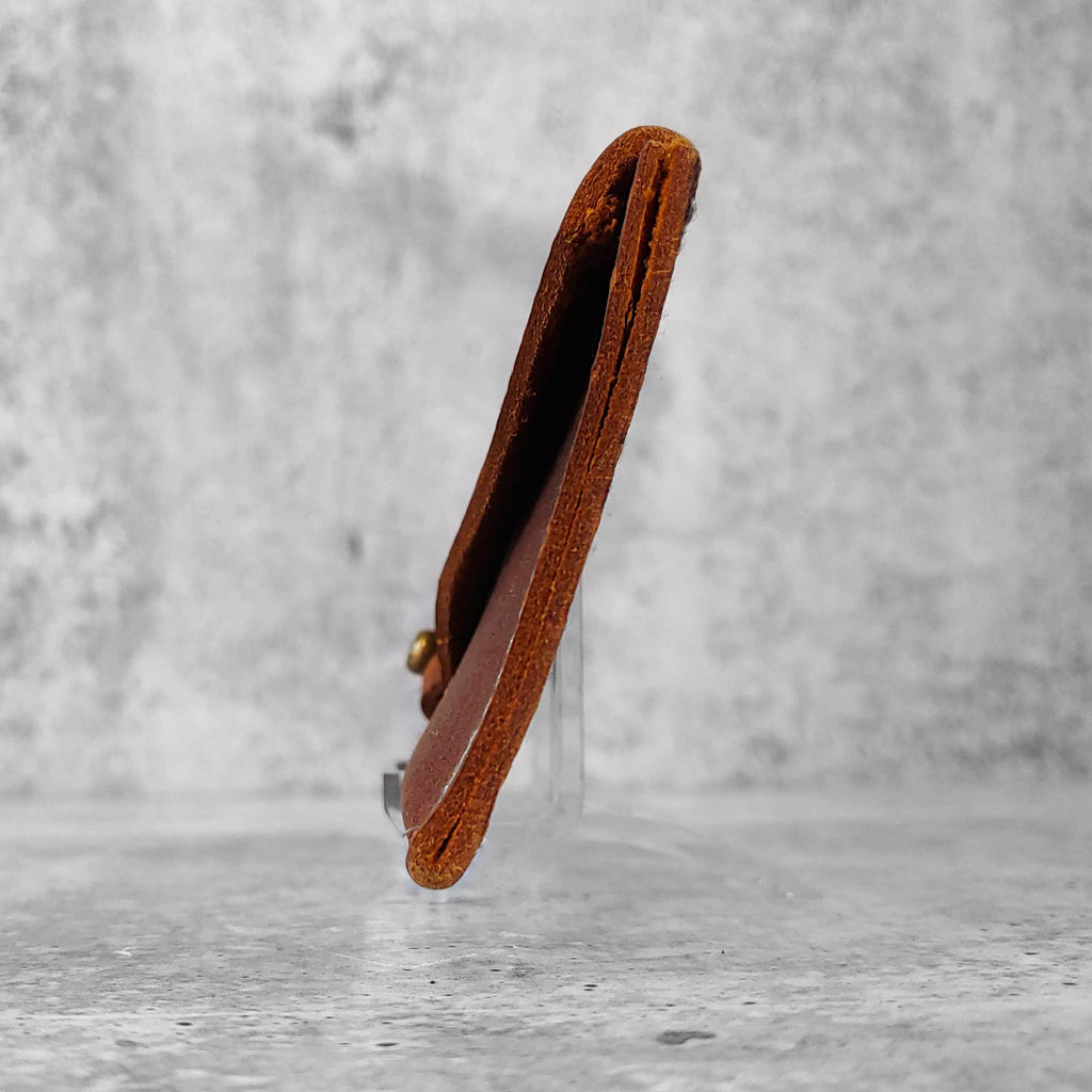"Side view of ""slim leather wallet"" in kodiak brown against a concrete background."