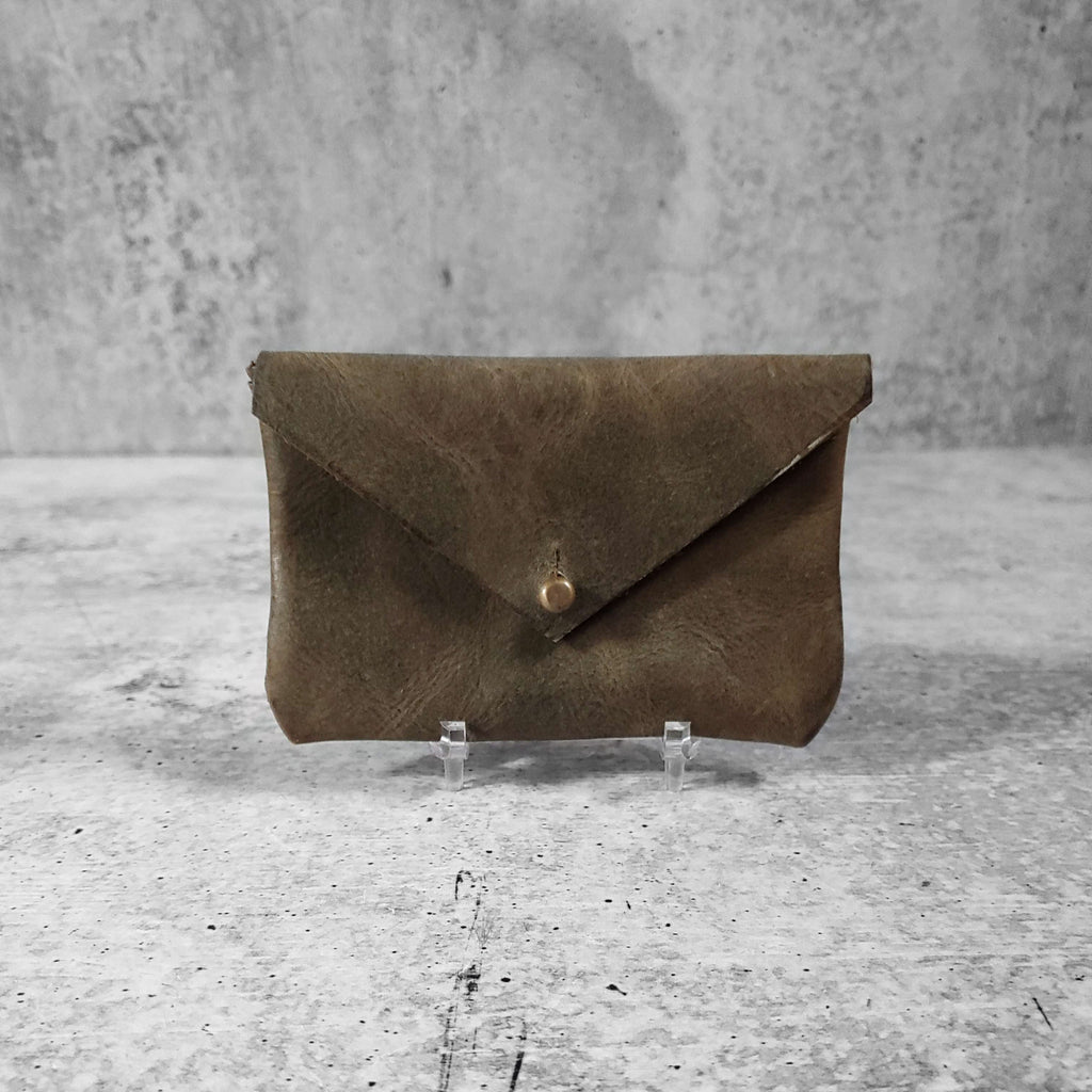 "Front facing view of ""smooth leather card holder"" in dark olive against a concrete background."