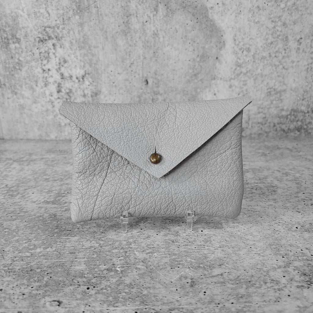 "Front facing view of ""soft leather card holder"" in concrete grey against a concrete background."