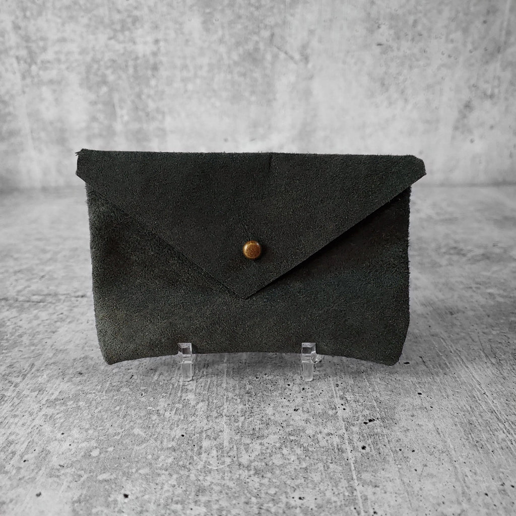 "Front facing view of ""soft leather card holder"" in rosemary against a concrete background."