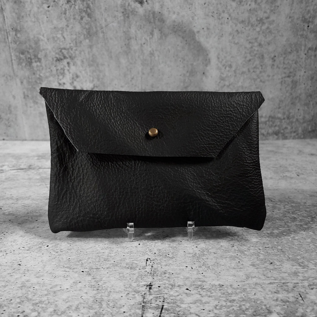 "Front facing view of ""soft leather clutch trapezoid"" in onyx against a concrete background."