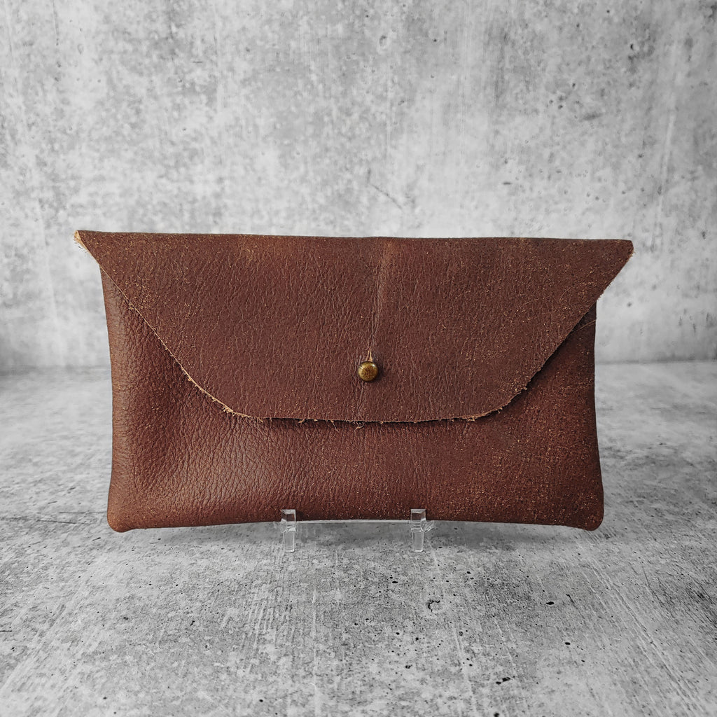 "Front facing view of ""soft leather clutch trapezoid"" in walnut against a concrete background."