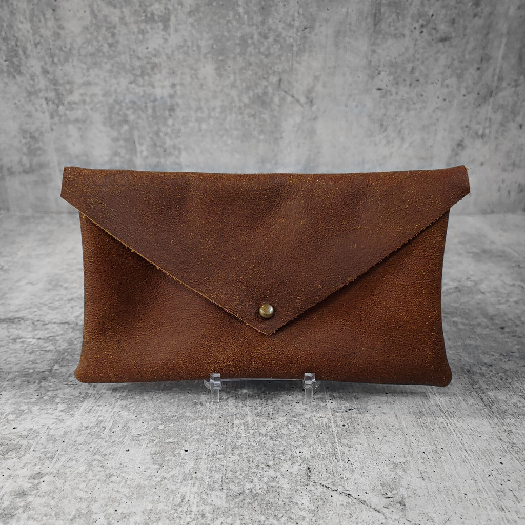 "Front facing view of ""soft leather clutch triangle"" in walnut against a concrete background."