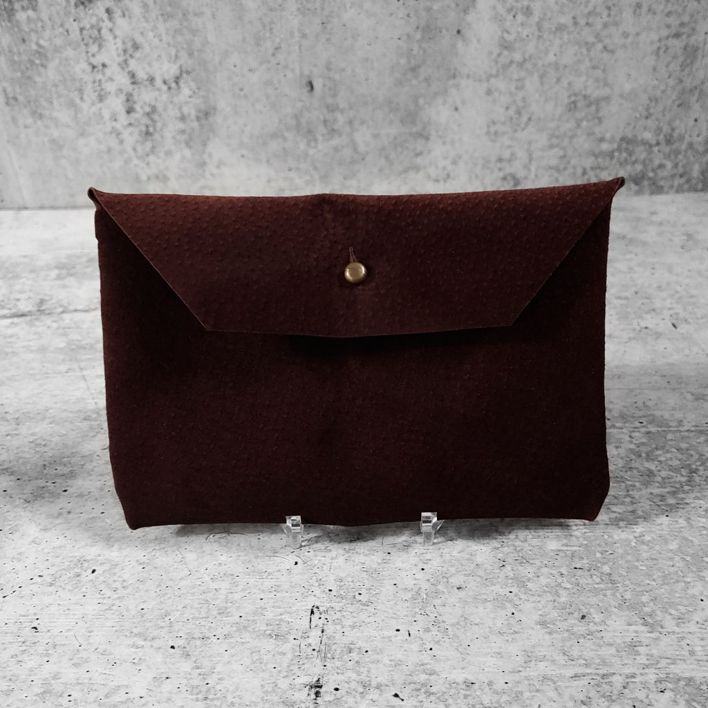 "Front facing view of ""soft suede clutch trapezoid"" in chocolate against a concrete background."