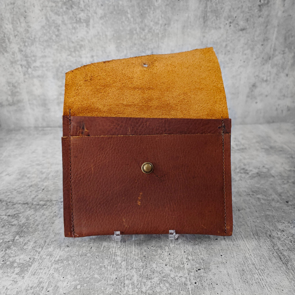 "Open, front facing view of ""wide leather wallet with asymmetric flap"" in kodiak brown against a concrete background. Inside pocket visible."