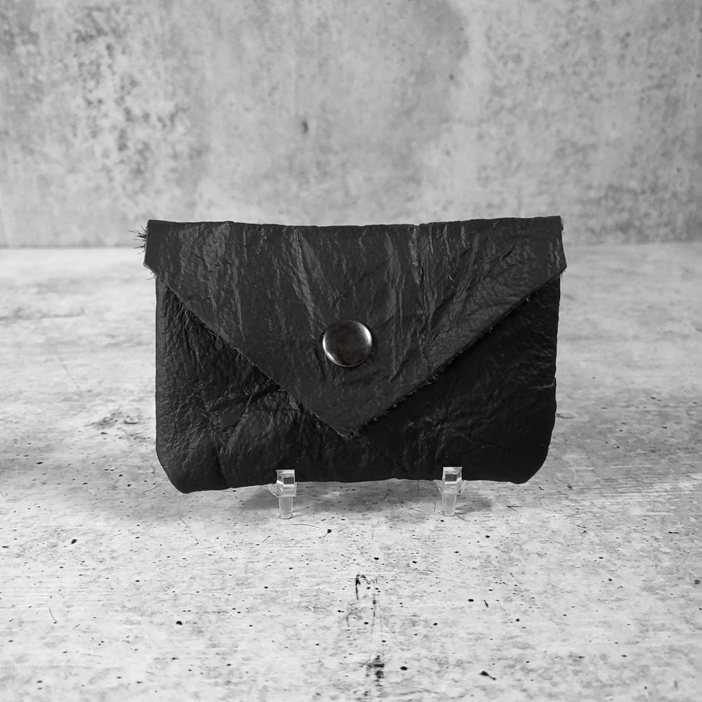 "Front facing view of ""wrinkled soft leather card holder"" in onyx against a concrete background."