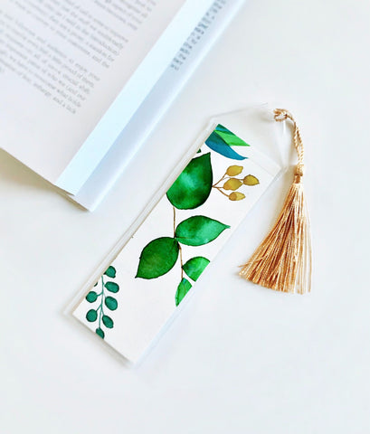watercolor painting inside a plastic bookmark sleeve with golden tassel