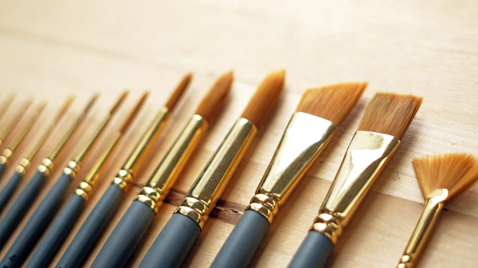 a close up of multiple paintbrushes in a row on a table