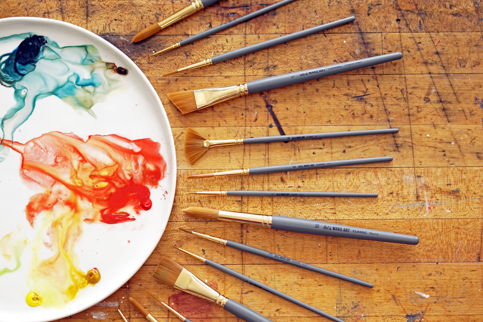 paint palette with variety of brushes styled around it