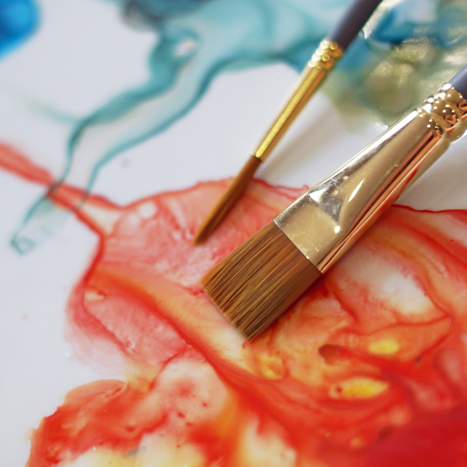 close up of two paintbrushes on a paint palette