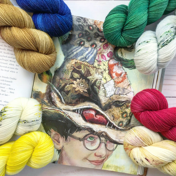 Eight Hogwarts House colored skeins of yarn around an image of Harry Potter in the Sorting Hat