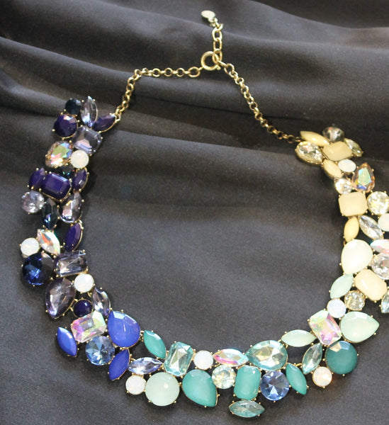 Gold tone necklace with multi colored and shaped stones.