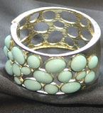 Gold tone clasp bracelet with light green stones