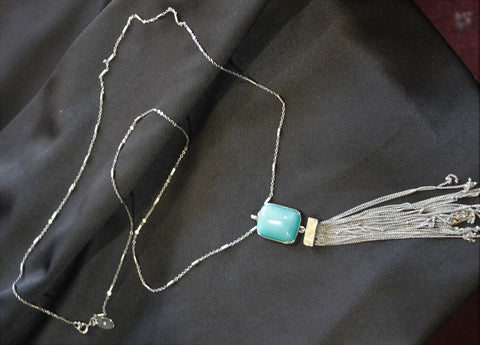 30 inch silver tone necklace with turquoise colored stone and silver tone fringe.