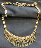 Gold tone, heavy links necklace with fringe and clear stone and onyx beads.