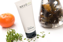 NEUÚ Shave Gel surrounded by seaweed in a glass jar, mandarin orange and marjoram leaf, with skincare tips to help your skin look its best