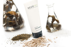 NEUÚ Face scrub surrounded by glass jars of seaweed and contains sunflower seed oil which contains Vitamin D, which is the third vitamin of what vitamins are good for skin