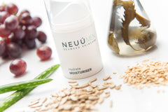 NEUÚ Moisturiser surrounded by ingredients of red grapes, aloe plant, seaweed in a glass, oats and seeds which helps to reduce redness of the skin