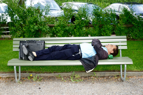 business man sleeping on wooden park bench, representing sleep which will help men look younger