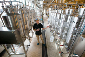 Deschutes Brewery assistant brewmaster Chris Dent flanked by rows of conical fermenters in their state of the art 2 bbl pilot brewing system