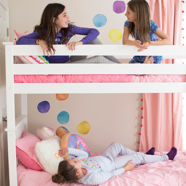 Two smiling children on top bunk on white bunk bed with slated headboard with angled ladder