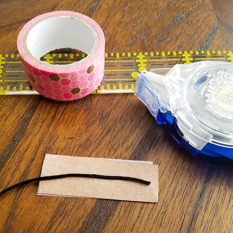Securing the String for DIY Washi Tape Feather Bookmarks