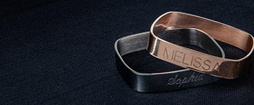 Two engraved rings on a black background