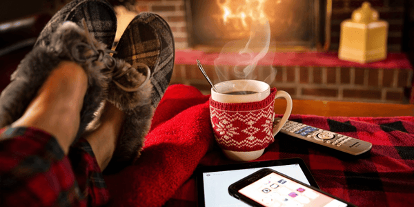 Example of a person lowering stress levels by sitting near a warm fireplace with a cup of hot chocolate.