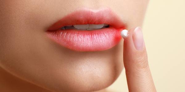 A woman with an early cold sore symptom, treating her lip with Blister Balm® External Analgesic Ointment.