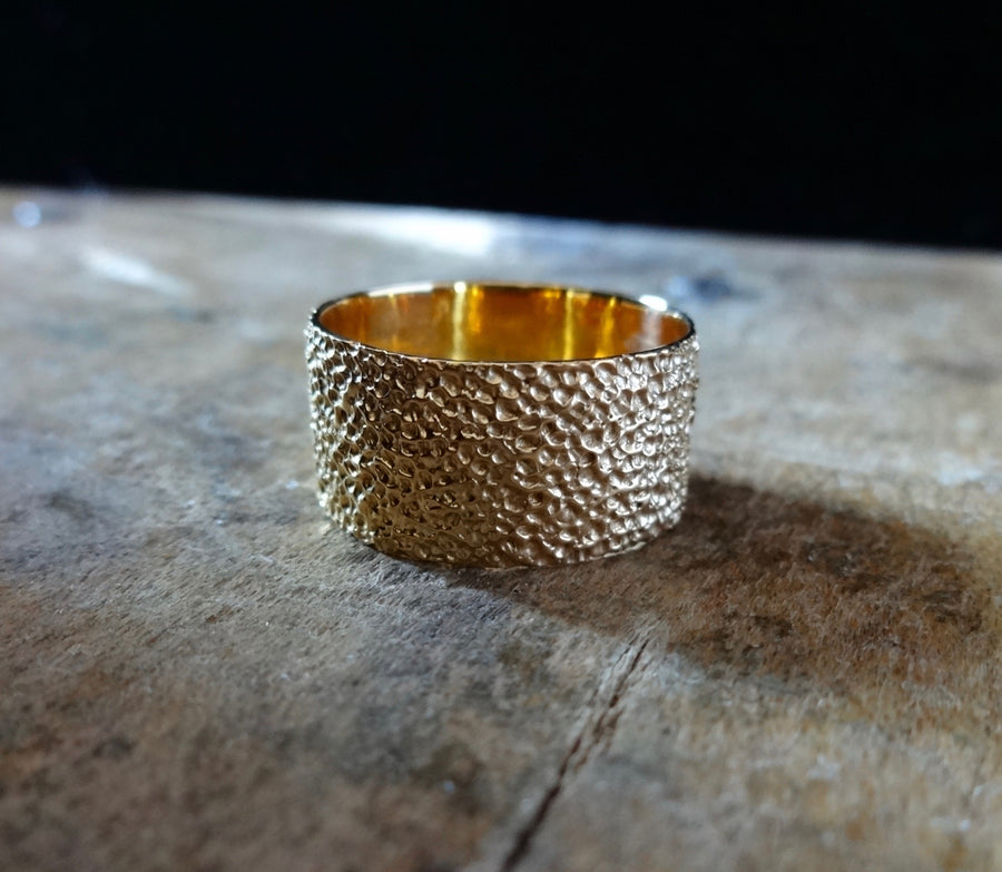 Simple elegant broad ring bands hand textured to emulate the dappled light naturally found in nature handmade in NYC by designer Jayne Moore model Jayne Moore from recycled refined metals in 18kt gold a light classic timeless wedding band for him or for her