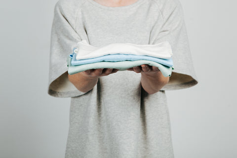 Raglan luxe pullover holding folded linen tshirts