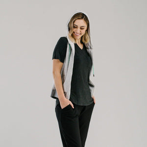 Light grey vest with white lined hood and mint drawstring cords, worn with v-neck tshirt and slouch pants