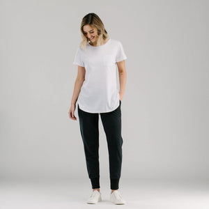 White long t-shirt with scoop hem and front patch pocket styled with black slouchy pants