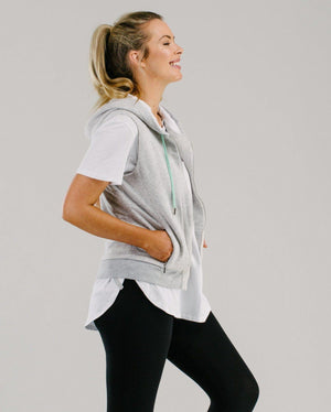 Light grey vest with white lined hood and mint drawstring cords, worn with long white t-shirt and black legging side view