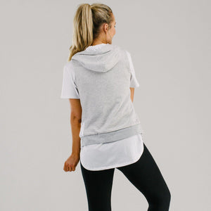 Light grey vest with white lined hood and mint drawstring cords, worn with long white t-shirt and black legging back view