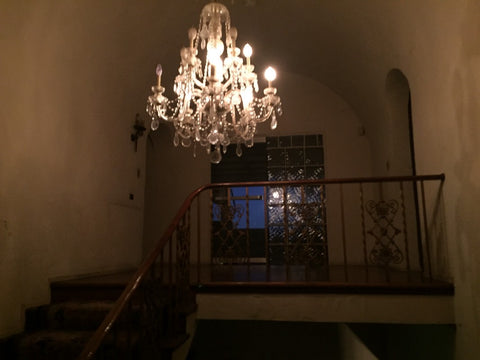 The massive chandelier that lights the top of the stairs.