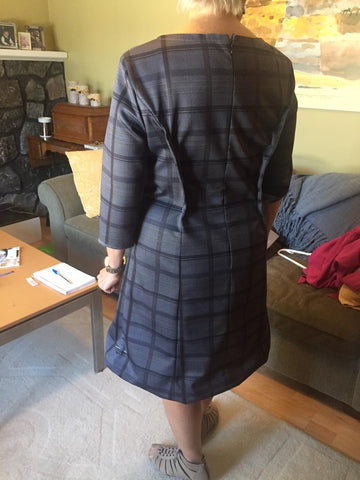 The back view of the honorable Cathy Rogers wearing the grey tartan dress, during the fitting for the Design for Change event to be held in Moncton, April 14th, 2018.