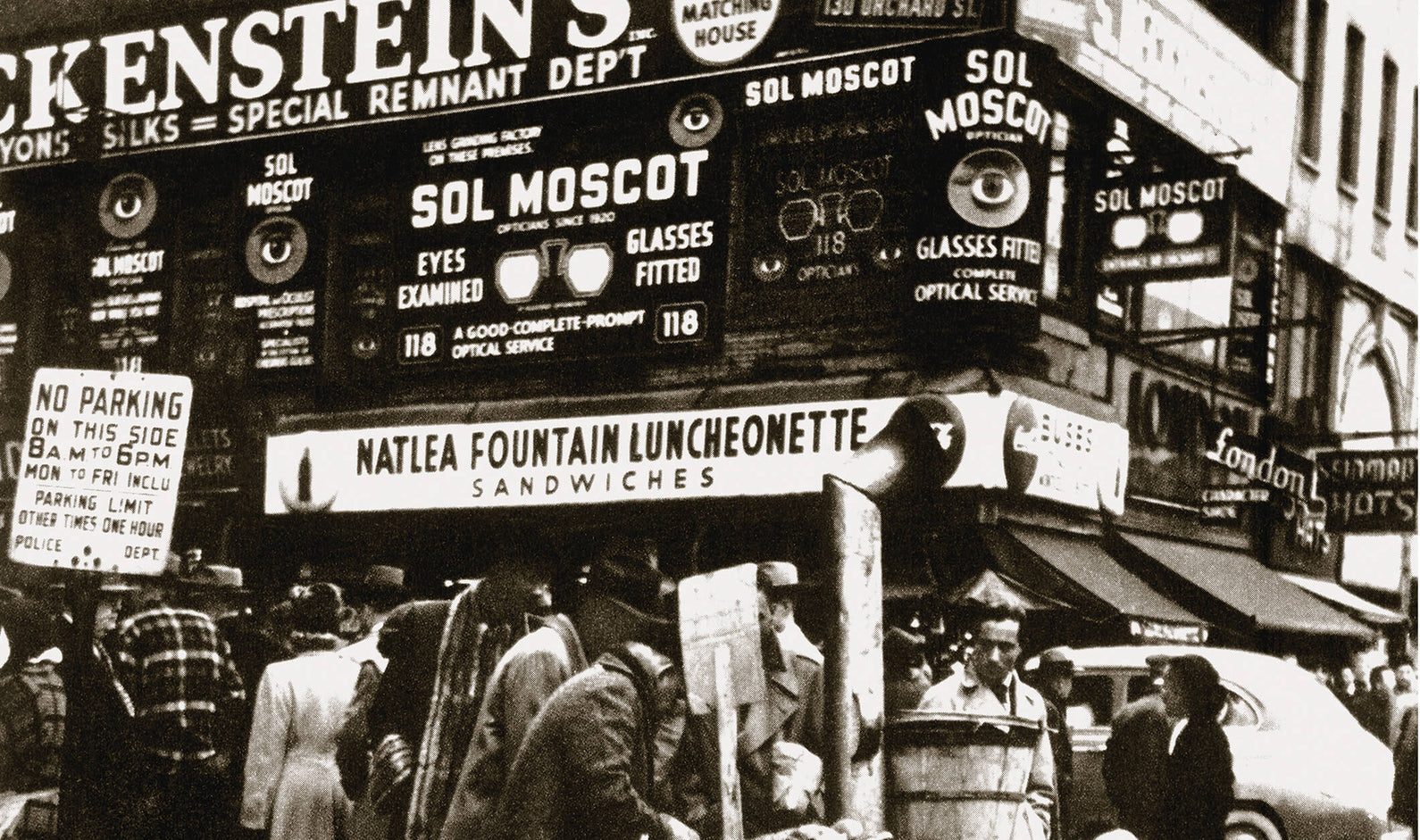 Black and white photo of Moscot store on busy street corner