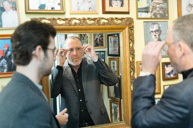 Man trying on glasses and looking in mirror