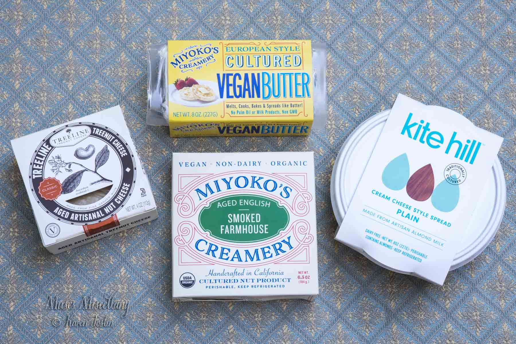 Photo of packaged vegan dairy alternatives, including Treeline Treenut Cheese, Miyoko's Creamery European Style Cultured Vegan Butter, Kite Hill Plain Cream Cheese, and Miyoko's Creamery Smoked Farmhouse cheese.